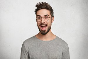 Excited funny joyful bearded male student wears optical round glasses, being amazed to recieve high grant, can`t believe in success, isolated over white background. Happy male worker rejoice promotion