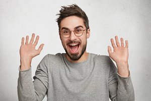 I am not guilty! Cheerful stylish fashionable young hipster guy in eyewear raises hands as shows being uninvolved, has happy look, isolated over white background. Caucasian male gestures in studio