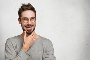 Positive bearded thoughtful male has brilliant idea, wants to realize it, keeps hand on chin, poses against white background with copy space for your advertismet. People, youth, facial expressions