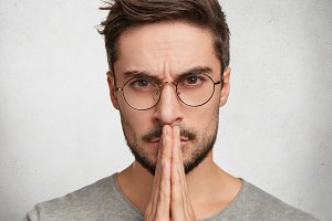 Close up portrait of serious faithful bearded young male wears spectacles, keeps palms together, hopes for better and good luck, looks confidently directly into camera. Desire, wish concept.