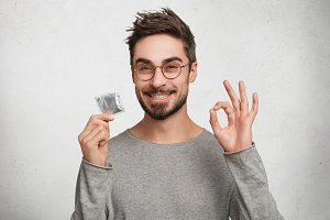 Portrait of happy smiling male with bristle shows ok sign as holds condomn, agrees to spend night with beautiful woman. Caucasian bearded guy advertises new kind of contraceptive. Safety and health