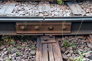 A close-up of rust metal rivets. Old sleepers, in city there is a tram line. In nature, a wet wooden board. Coupling of metal rails.