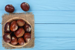 chestnut in bowl on blue wooden background with copy space for your text. Top view. Flat lay