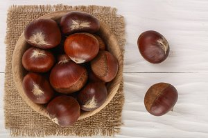 chestnut in bowl on white wooden background. Top view. Flat lay