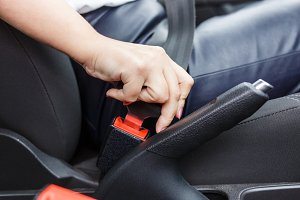 Young woman fastening seat belt in the car