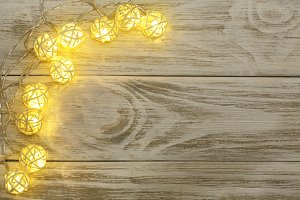 christmas garland lights on old wooden background with copy space for your text. Top view