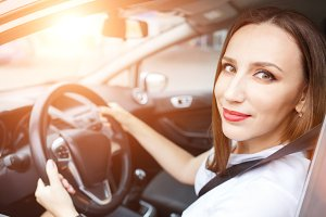 Young woman studying driving car in school