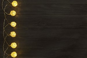christmas garland lights on black wooden background with copy space for your text. Top view