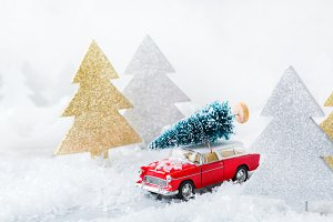 Toy car carrying christmas tree in a snow forest