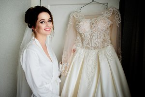 Pretty bride stands before a dress