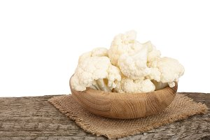 Piece of cauliflower in bowl on wooden table with white background