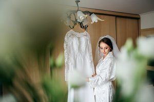 Bride standing before a dress