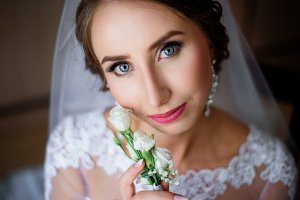 Bride holds white rose boutonniere