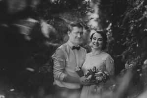 Black and white photo the bride and groom in the foliage of trees
