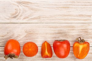 persimmon on white wooden background with copy space for your text. Top view. Flat lay pattern