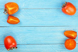 persimmon on blue wooden background with copy space for your text. Top view. Flat lay pattern