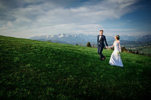 Bride and groom walk on a field