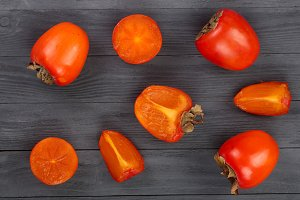 persimmon on black wooden background. Top view. Flat lay pattern