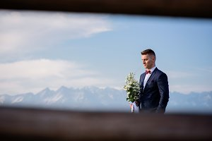 Groom stands with wedding bouquet