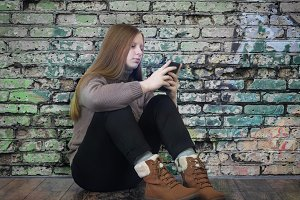Beautiful teen girl sitting with a mobile phone