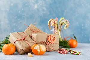 Christmas gift box, candy cane, tangerines and fir tree branch