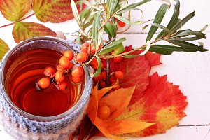 autumn herbal  tea sea buckthorn knitted in a mug on a white wooden background