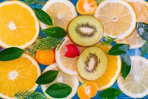 Fresh raspberry, kiwi, orange, lemon and orange slices floating in water on white