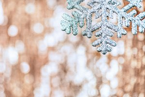 Shining Christmas snowflake on abstract shimmering bokeh backgro