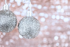 Shining Christmas balls on abstract shimmering bokeh background