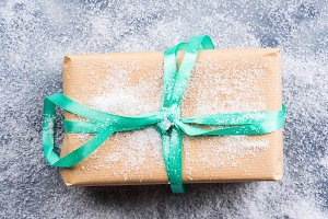 Gift box with green ribbon and snow