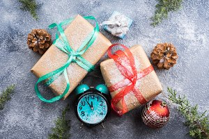 Christmas gifts with ribbons and snow. Clock