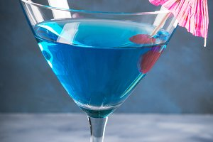 Blue cocktail in martini glass with umbrella