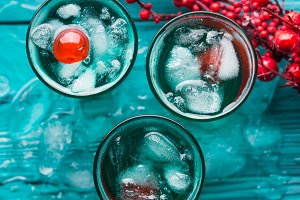 Short alcohol green drinks with cherry