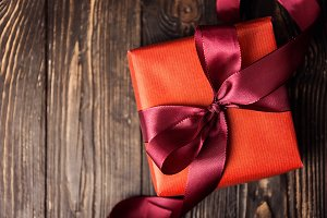 Closeup of red gift on wooden table