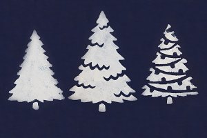 Three white Christmas trees painted with paint through a stencil on a dark blue background.