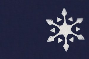 One white snowflake painted with paint through a stencil on a dark blue background. Copy space.