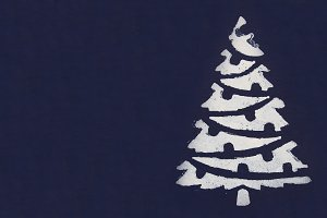One white Christmas tree painted with paint through a stencil on a dark blue background. Copy space.