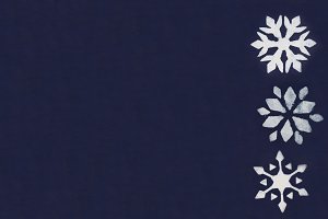 A few white snowflakes are painted through a stencil on a dark blue background. Copy space.