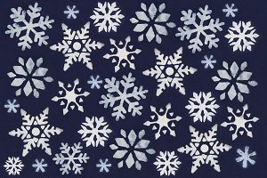 A lot of white snowflake painted with paint through a stencil on a dark blue background.