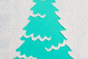 A trace from a stencil in the shape of a Christmas tree made of flour on a blue background. Ideas for festive baking and decorating.