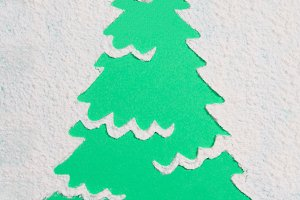 A trace from a stencil in the shape of a Christmas tree made of flour on a green background. Ideas for festive baking and decorating.