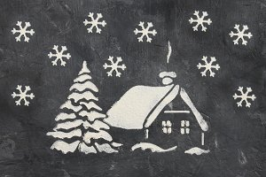 A trace from a stencil in the form of a Christmas tree and a house with snowflakes from flour on a gray concrete background. Ideas for festive baking and decorating.