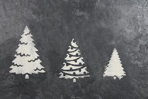 A trace from a stencil in the form of three Christmas trees made of flour on a gray concrete background. Ideas for festive baking and decorating.