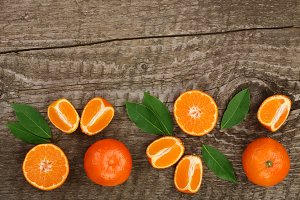 orange or tangerine with leaves on old wooden background. Flat lay, top view. Fruit composition