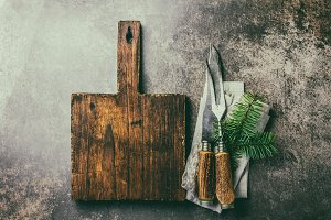 Vintage rustic cutlery set and wooden cutting board, Christmas decorations. Christmas menu background.