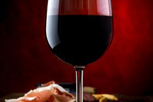 Glass of red wine and bord with ham serrano. Close up