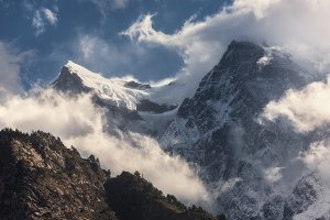 Majestical scene with mountains with snowy peaks in clouds