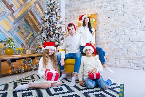 A Christmas photograph of a beautiful family with two children in Santa Claus red caps and red presents. Sit on the couch in the Christmas interior.