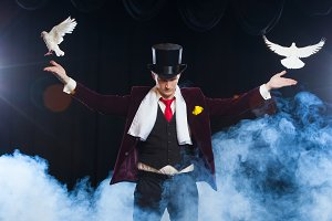 The magician with a two flying white Doves. on a black background shrouded in a beautiful mysterious smoke