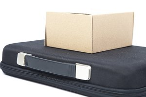 Brown paper box on a black briefcase